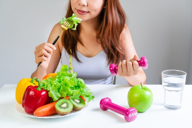 Junge asiatische frauen, die gemüse essen, während hantel mit obst, gemüse, wasser und maßband halten. auswahl gesunder lebensmittel. sauberes ess- und bewegungskonzept. organ