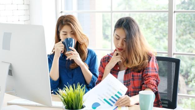 Junge asiatische frauen, die zu hause büro mit glücklichem gefühlmoment bearbeiten