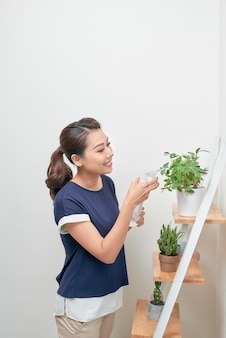 Junge asiatische frauen erhöhen das wasser zu pflanzen