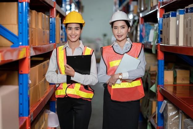 Junge asiatische frauen in sicherheitswesten, die an lagerfabrik stehen