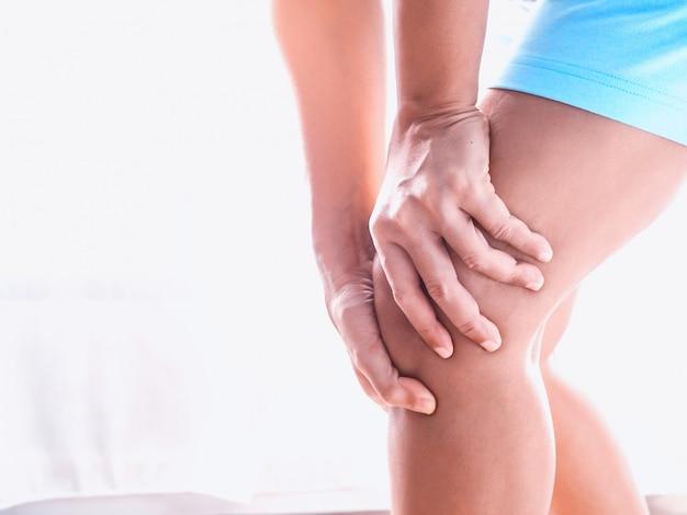 Junge asiatische frauen mit körperschmerzen, die muskelverletzung mit knieschmerzen und beinschmerzen leiden