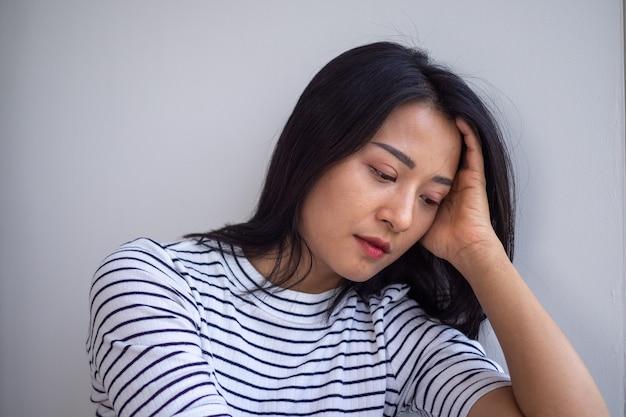 Junge asiatische frauen sind traurig und enttäuscht. frauen haben symptome einer depression. trauriges und einsames konzept