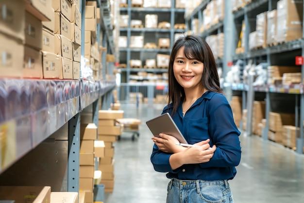Junge asiatische frauenprüfer- oder -praktikantenpersonalarbeit, die oben schaut und überprüft die zahl des einzelteilspeichers durch digitale tablette.