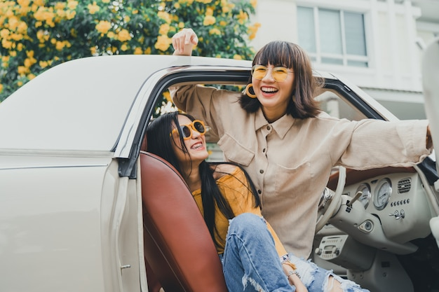 Junge asiatische freundinnen, die innerhalb eines autos lächeln
