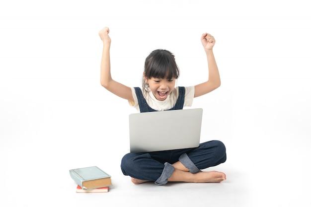 Junge asiatische frohe und glückliche studentin, die auf dem laptop lokalisiert auf weißem hintergrund schaut