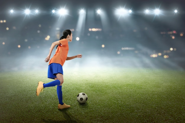 Junge asiatische fußballspielerfrau treten den ball