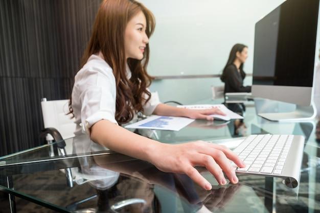 Junge asiatische geschäftsfrau der nahaufnahme hand, welche die tastatur drückt
