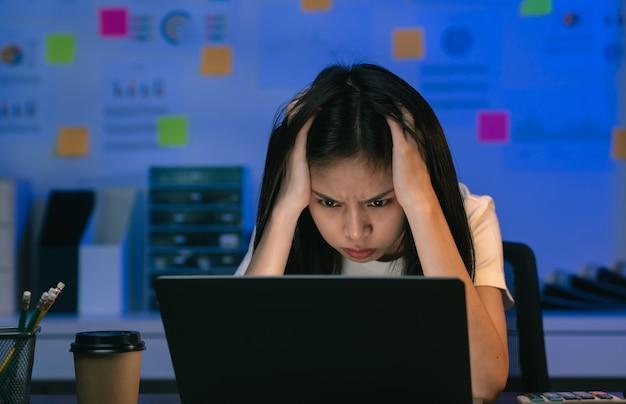 Junge asiatische geschäftsfrau, die am laptop arbeitet und nachts im büro kopfschmerzen hat.
