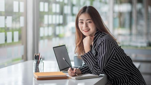 Junge asiatische geschäftsfrau, die am laptop arbeitet und zur kenntnis nimmt, während sie am tisch im büro sitzt