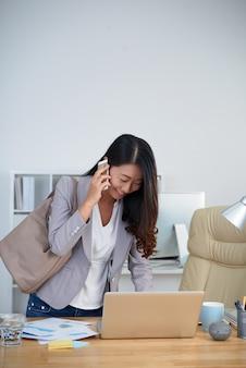 Junge asiatische geschäftsfrau, die am schreibtisch im büro steht, laptop verwendet und am telefon spricht