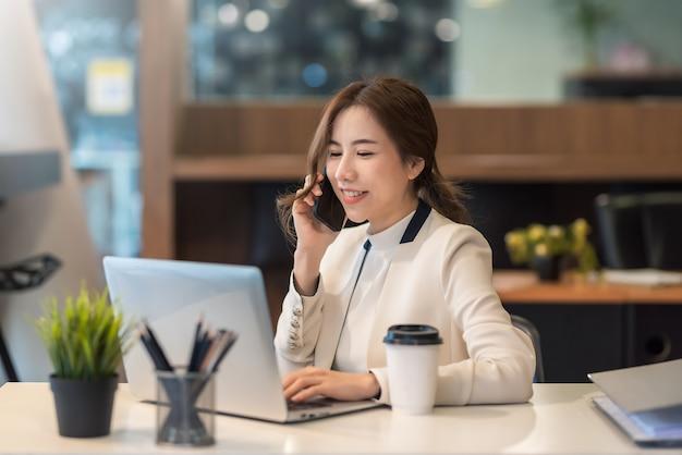 Junge asiatische geschäftsfrau, die am telefon spricht, während sie an einem laptop im büro arbeitet.