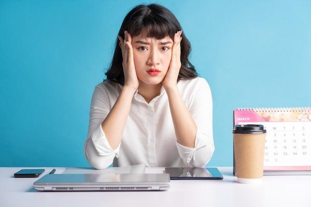 Junge asiatische geschäftsfrau, die an blau arbeitet