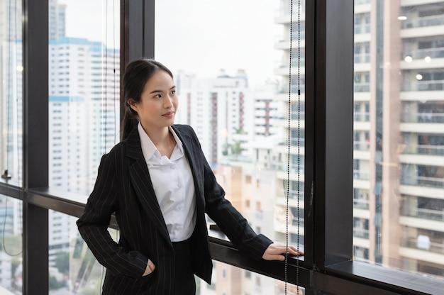 Junge asiatische geschäftsfrau, die durch fenster im büro steht und schaut