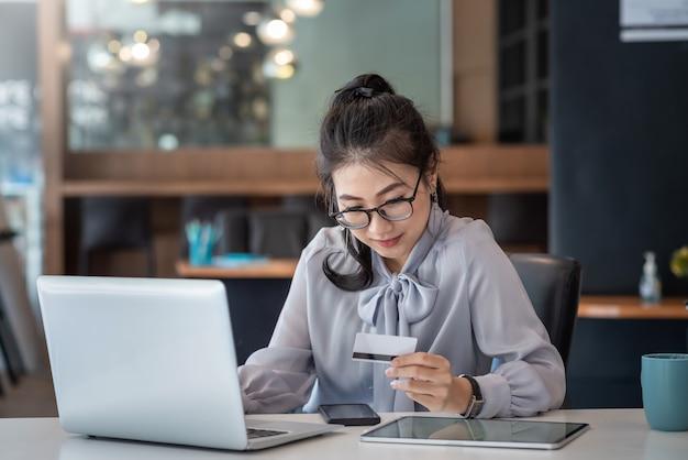 Junge asiatische geschäftsfrau, die eine kreditkarte hält und einen laptop für online-einkäufe im büro verwendet.