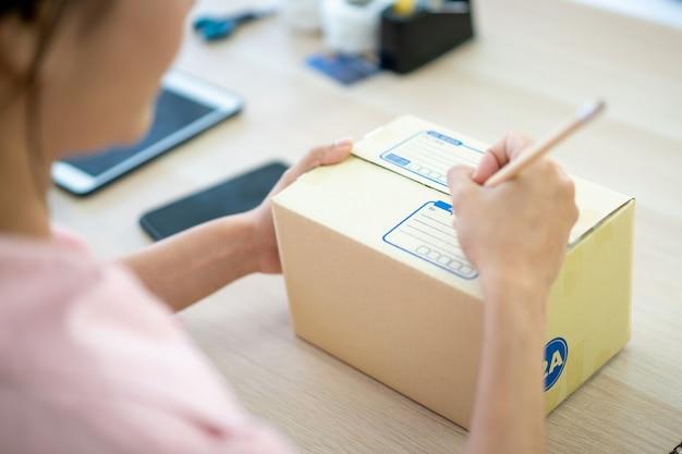 Junge asiatische geschäftsfrau, die einen briefkasten verpackt, um an kunden versendet zu werden. e-commerce-online-shopping-konzept. experte online-verkäufer verpackungskunden paketboxen für den versand.