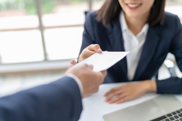 Junge asiatische geschäftsfrau, die gehalt oder prämiengeld vom manager im büro empfängt.