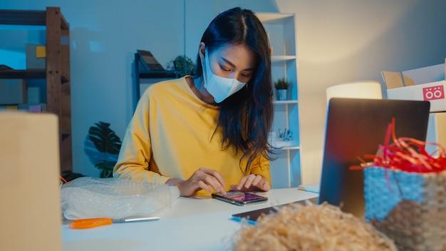 Junge asiatische geschäftsfrau, die gesichtsmaske trägt, die bestellung auf smartphone prüft