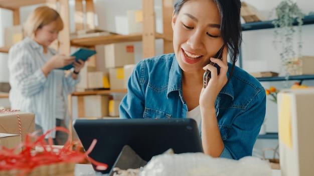 Junge asiatische geschäftsfrau, die gesichtsmaske unter verwendung des mobiltelefons trägt, das bestellung erhält und produkt auf lagerarbeit zu hause büro prüft