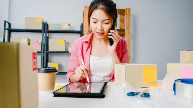Junge asiatische geschäftsfrau, die handyanruf verwendet, der bestellung empfängt und produkt auf lager überprüft, arbeit zu hause büro. kleinunternehmer, online-marktzustellung, freiberufliches lifestyle-konzept.