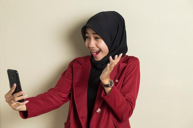 Junge asiatische geschäftsfrau, die hijab trägt, der einen videoanruf unter verwendung des smartphones macht