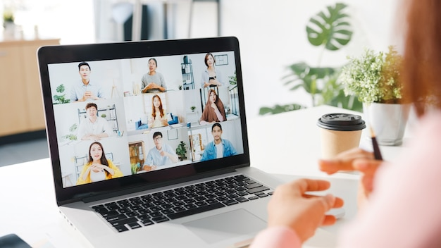 Junge asiatische geschäftsfrau, die laptop verwendet, spricht mit kollegin über plan in videoanrufbesprechung, während sie von zu hause aus im wohnzimmer arbeitet.