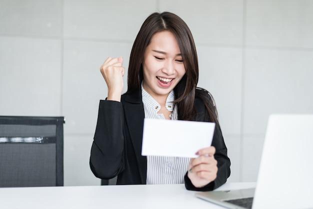 Junge asiatische geschäftsfrau, die nach dem empfangen des prämiengeldes oder -gehalts glücklich sich fühlt.