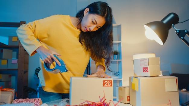 Junge asiatische geschäftsfrau, die produkt unter verwendung der bandverpackungsbox für das senden an kundenbestellung im heimbüro in der nacht vorbereitet