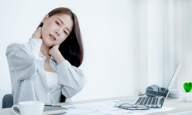 Junge asiatische geschäftsfrau, die schmerzen fühlt und sich streckt, nachdem sie lange zeit hart am computer-laptop gearbeitet hat