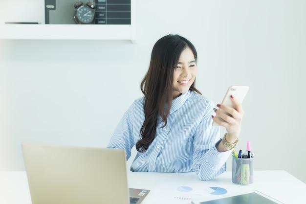 Junge asiatische geschäftsfrau, die smartphone für das arbeiten am schreibtisch verwendet