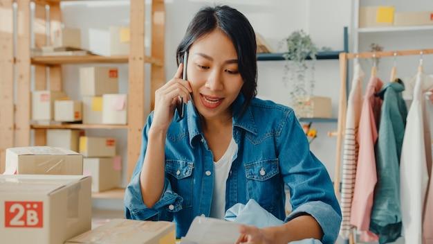 Junge asiatische geschäftsfrau, die smartphone verwendet, das bestellung empfängt und produkt auf lagerarbeit zu hause büro prüft