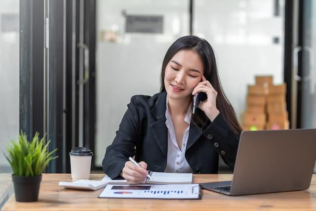 Junge asiatische geschäftsfrau, die stift mit diagramm hält, das am telefon im büro spricht.