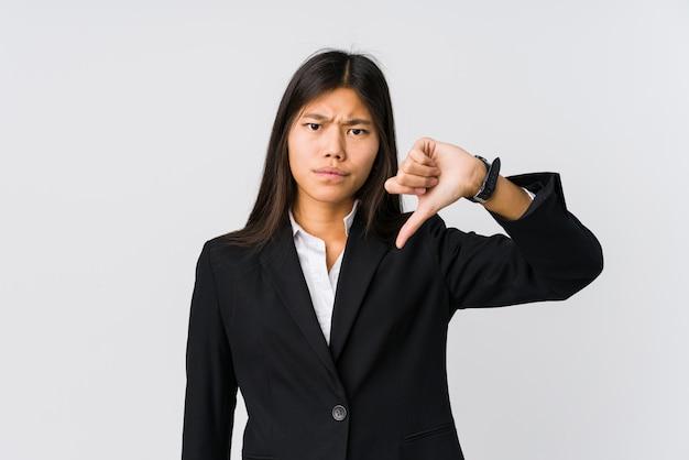 Junge asiatische geschäftsfrau, die unten eine abneigungsgeste, daumen zeigt. uneinigkeit konzept.