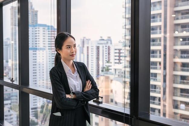 Junge asiatische geschäftsfrau, die verschränkte arme durch fenster im modernen büro am geschäftsviertel steht