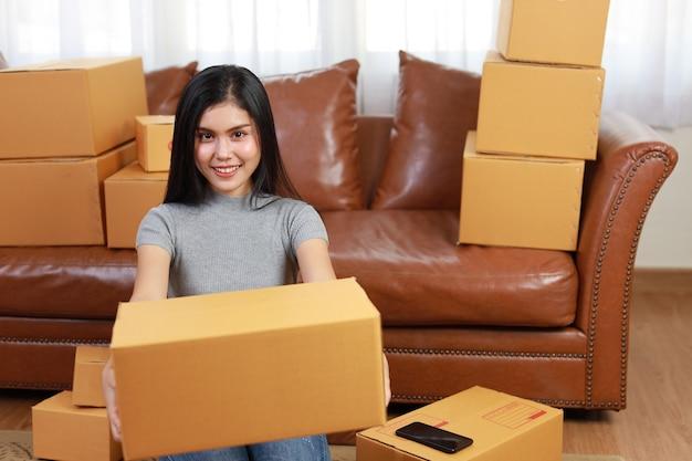 Junge asiatische geschäftsfrau, die von zu hause aus mit smartphone und online-einkaufsauftragsbox hält und arbeitet