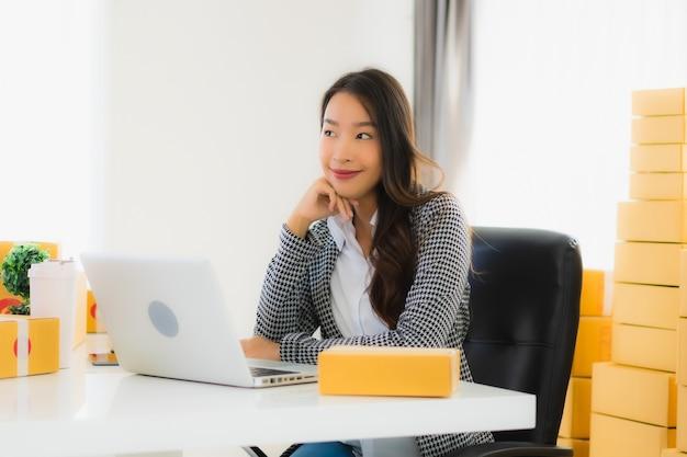 Junge asiatische geschäftsfrau, die von zu hause mit laptop arbeitet