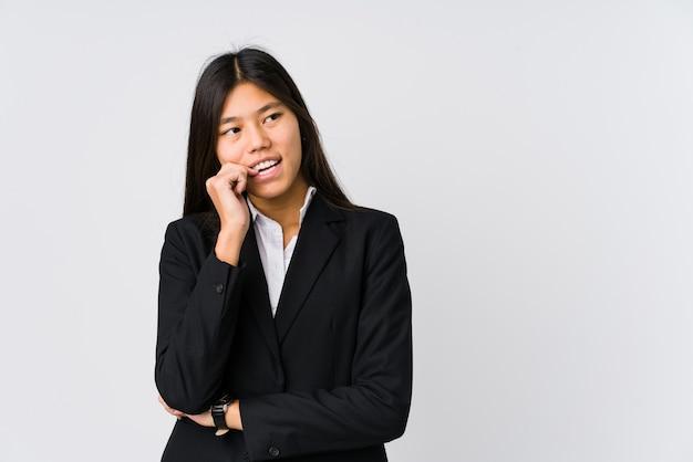 Junge asiatische geschäftsfrau entspannte sich und dachte über etwas nach, das einen kopierraum betrachtete.