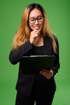 Junge asiatische geschäftsfrau gegen grünflächen