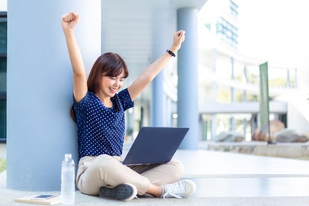 Junge asiatische geschäftsfrau hebt aufgeregt die arme, während sie auf ihren laptop schaut