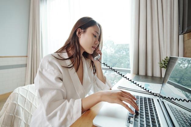Junge asiatische geschäftsfrau im bademantel, die mit kollegen telefoniert und details des verkaufsberichts bespricht