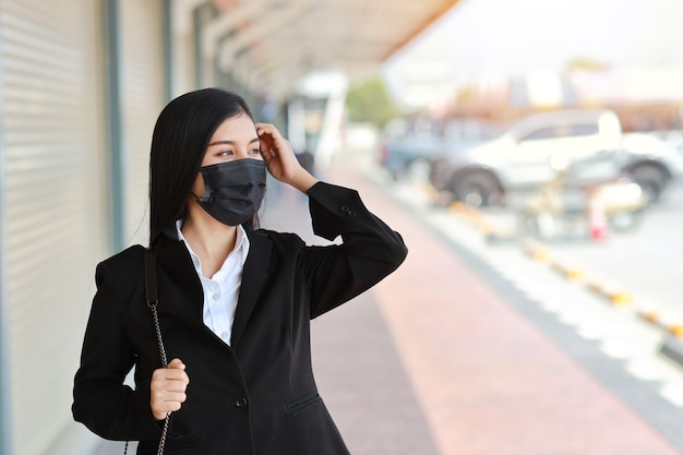 Junge asiatische geschäftsfrau im geschäftsschwarzanzug mit schutzmaske für das gesundheitswesen, das auf der straße im freien und auf der suche geht
