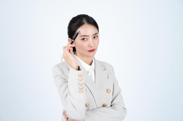 Junge asiatische geschäftsfrau im grauen anzug, ist klug und selbstbewusst. manager denkt über arbeit nach.