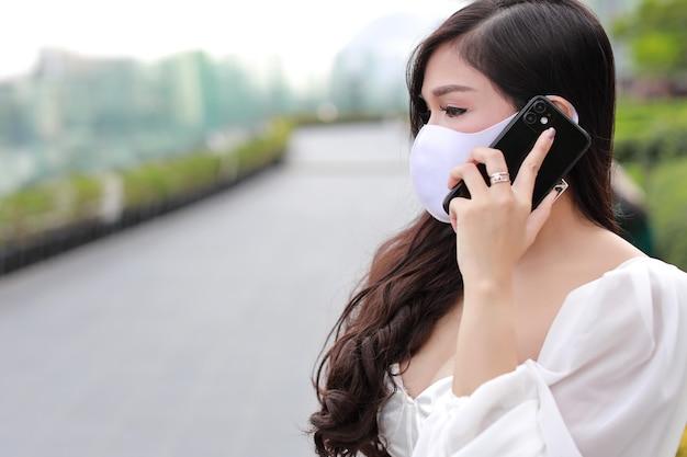 Junge asiatische geschäftsfrau im weißen lässigen kleid mit schutzmaske für gesundheitswesen, im öffentlichen freien gehend und am smartphone arbeitend