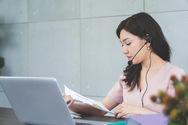 Junge asiatische geschäftsfrau in kopfhörern mit computer, die online-vdo-konferenztreffen haben