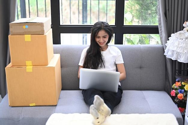 Junge asiatische geschäftsfrau, inhaberin von kmu online mit laptop, erhält eine bestellung vom kunden, während sie auf dem sofa in ihrem startup-homeoffice sitzt.