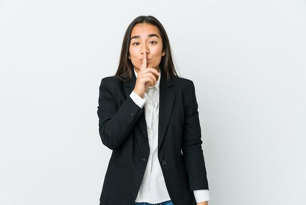 Junge asiatische geschäftsfrau lokalisiert auf weißer wand, die ein geheimnis hält oder um stille bittet.