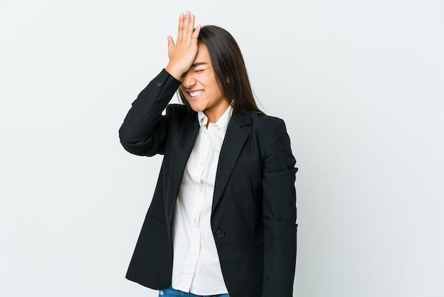 Junge asiatische geschäftsfrau lokalisiert auf weißer wand, die etwas vergisst, stirn mit handfläche schlägt und augen schließt.