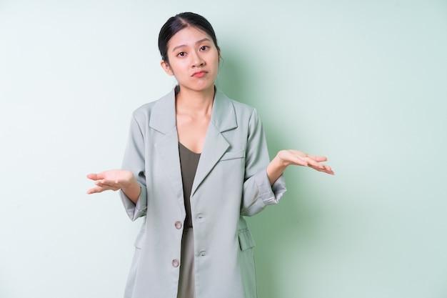 Junge asiatische geschäftsfrau mit grünem anzug auf grünem hintergrund