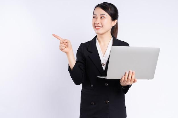 Junge asiatische geschäftsfrau mit laptop auf weißem hintergrund
