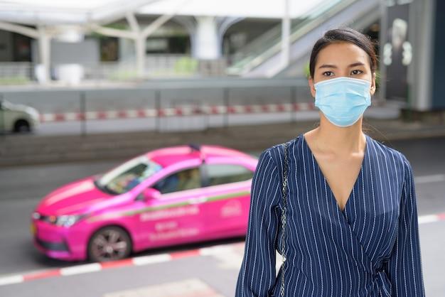 Junge asiatische geschäftsfrau mit maske an der taxistation in den stadtstraßen