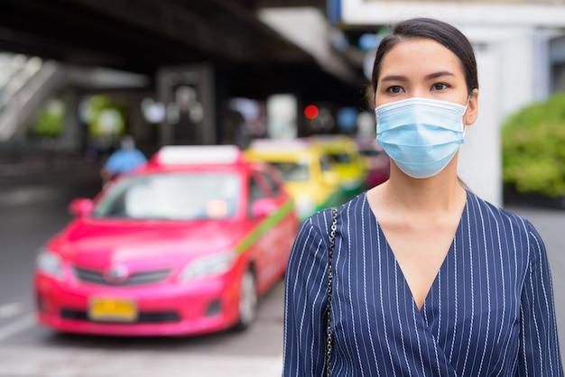 Junge asiatische geschäftsfrau mit maske, die an der taxistation in den stadtstraßen denkt